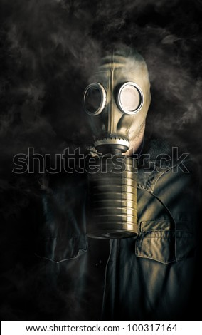 Soldier in a gas mask and canister with fumes swirling about his head in the darkness in a biohazard, death and destruction concept - stock photo