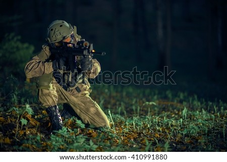 Soldier in Action at Night. Military Operation Concept. - stock photo