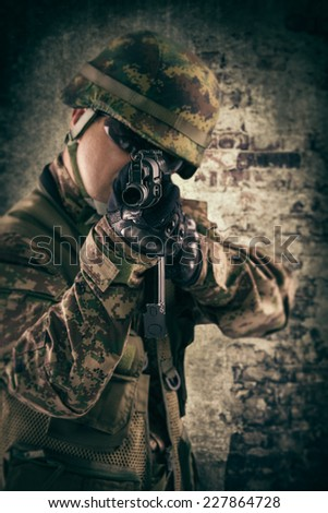 Soldier in action, shooting from a gun