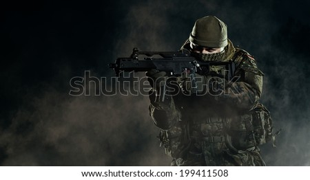 Soldier in an attack/defensive position. Going up in smoke. Destroyed object. - stock photo