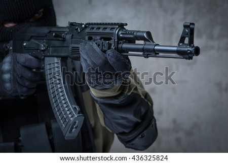 Soldier in balaclava and camouflage with automatic rifle in hands - stock photo