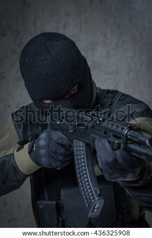 Soldier in balaclava and camouflage with automatic rifle in hands