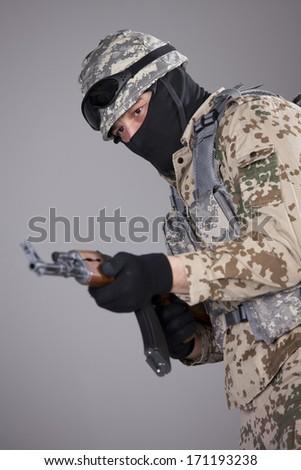 Soldier in camouflage a with kalashnikov machine gun in a studio - stock photo