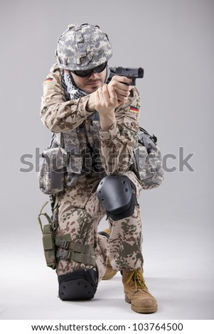 Soldier in camouflage aiming with gun in a white studio