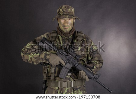 Soldier in camouflage and modern weapon M4 on black background - stock photo