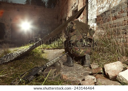 Soldier in camouflage battle uniform on location of suburban ruins - stock photo
