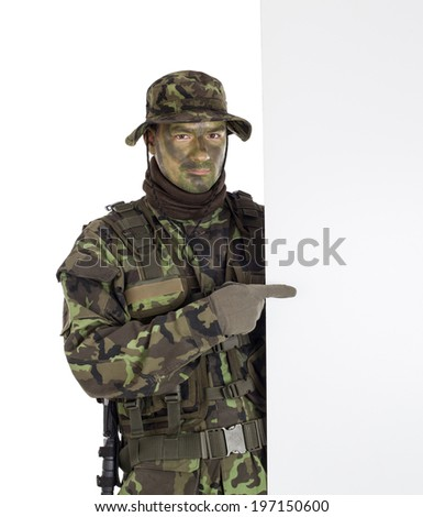 Soldier in camouflage pointing finger to white blank board - stock photo