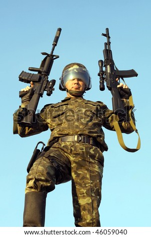 Soldier in camouflage staying with two guns