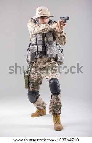 Soldier in camouflage uniform with a handgun aiming - shot in white studio - stock photo