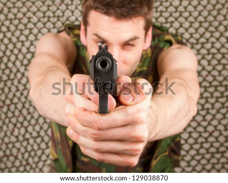 Soldier in camouflage vest is holding a gun, isolated - stock photo