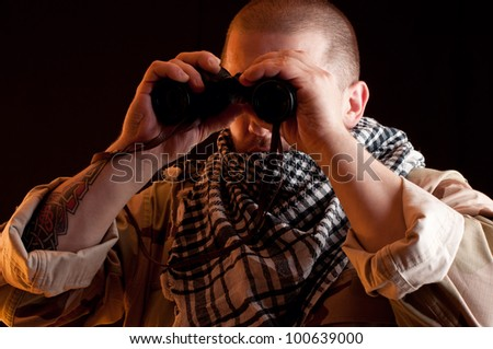 Soldier in camouflage with binoculars, black background
