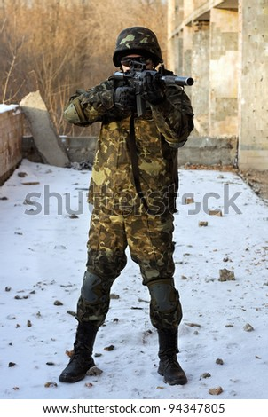 Soldier in camouflage with rifle in his hands - stock photo