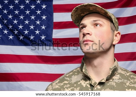 Soldier in camouflage with USA flag on background