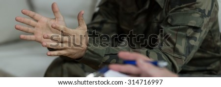Soldier in green military uniform - closeup of hands