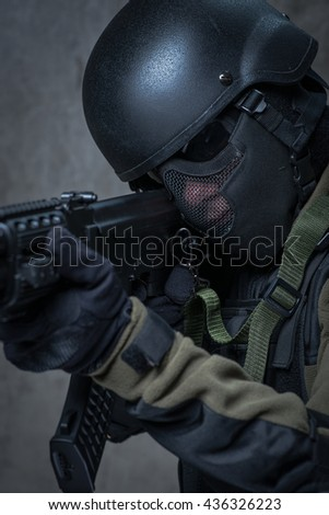 Soldier in helmet and camouflage with automatic rifle in hands