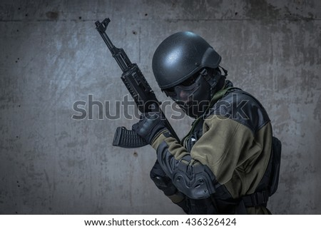 Soldier in helmet and camouflage with automatic rifle in hands - stock photo