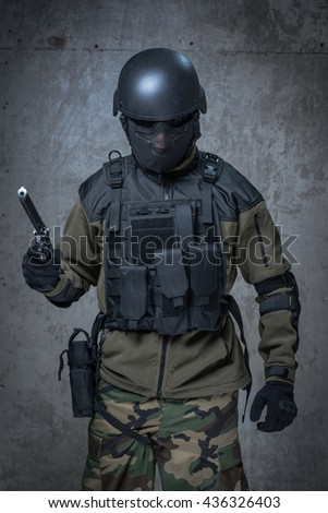 Soldier in helmet and camouflage with big gun in hands