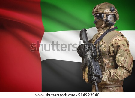 Soldier in helmet holding machine gun with national flag on background - United Arab Emirates