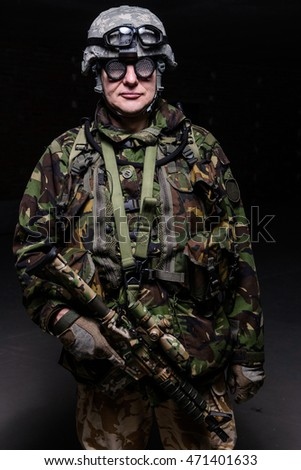 Soldier in helmet, weird glasses with rifle on dark background/Soldier in helmet with rifle