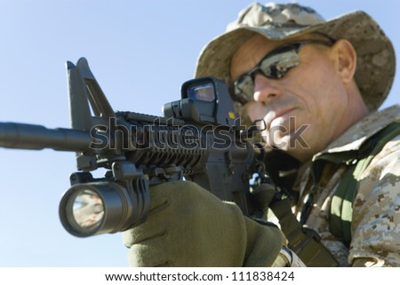 Soldier in sunglasses with assault rifles on a mission - stock photo