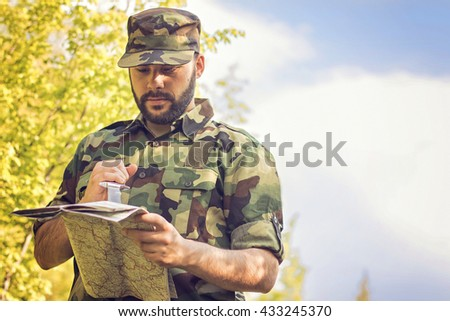 Soldier in the forest looking at his map, tries to find the right strategy.