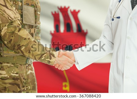 Soldier in uniform and doctor shaking hands with national flag on background - Gibraltar - stock photo