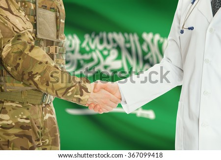 Soldier in uniform and doctor shaking hands with national flag on background - Saudi Arabia - stock photo