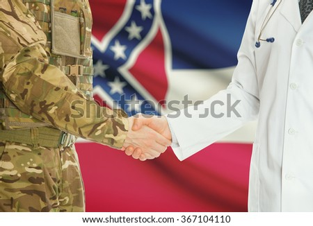 Soldier in uniform and doctor shaking hands with US states flags on background - Mississippi