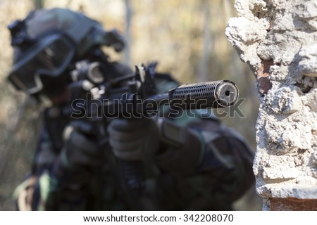 soldier in uniform take aim behind the wall - stock photo
