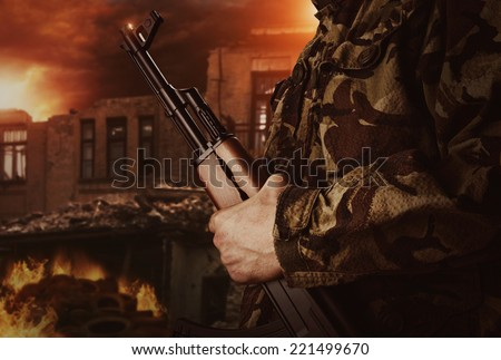 Soldier is holding gun on apocalyptic background - stock photo