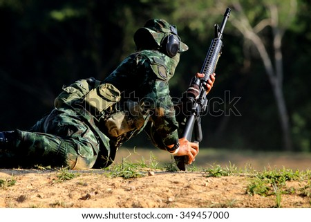 soldier is shooting rifle at goal - stock photo