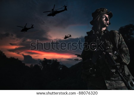 soldier looking victorious with apache helicopter fly past - stock photo