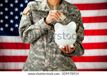 Soldier: Military Female Putting Money In Piggy Bank - stock photo