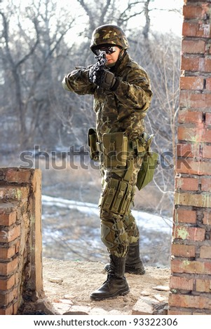 Soldier near wall with a gun in his hands - stock photo