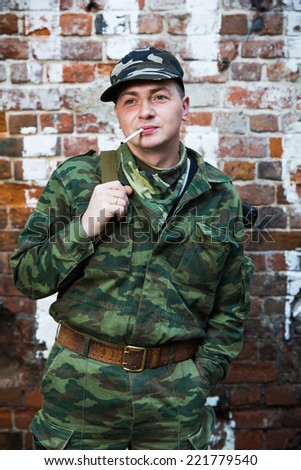 Soldier or militiaman in camouflage with assault rifle AK-74 stay near brick wall - stock photo