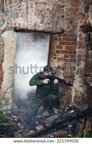 Soldier or militiaman in camouflage with assault rifle fighting in ruins