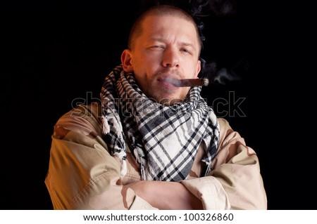 Soldier puffing some good cigar smoke, dark background - stock photo