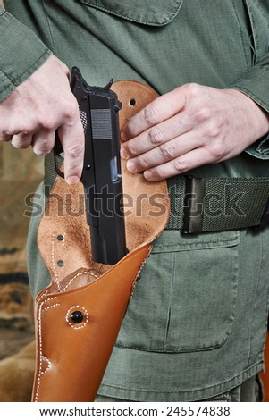 Soldier puts the gun in the holster - stock photo