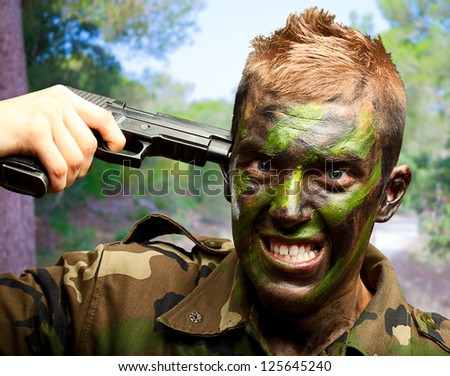 Soldier Putting Gunshot On Head at a park - stock photo