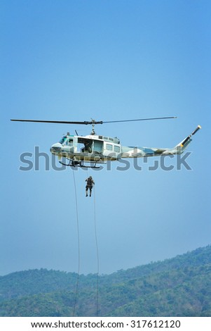 Soldier rappelling from a helicopter - stock photo
