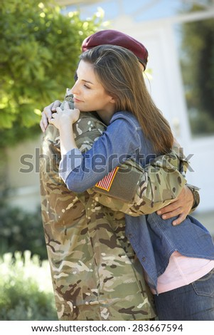 Soldier Returning Home And Greeted By Wife - stock photo