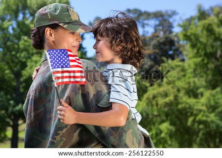 Soldier reunited with her son on a sunny day - stock photo