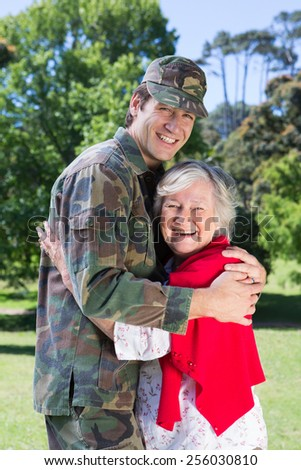 Soldier reunited with his mother on a sunny day - stock photo