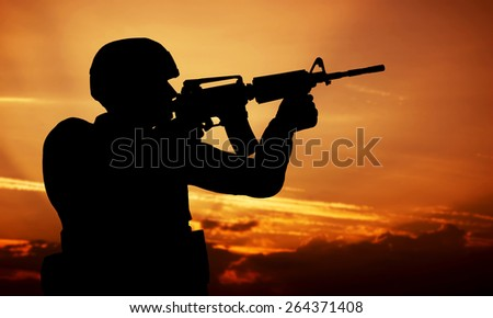 Soldier shooting with his weapon, rifle at sunset. War, army, military. - stock photo