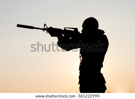 Soldier shooting with weapon gun at sunset. War, army, military