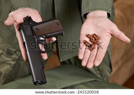 Soldier shows pistols Colt and ammunition cartridges closeup - stock photo