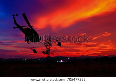 soldier silhouette in rappelling climb down from helicopter on sunset, Concept stop warfare with copy space add text