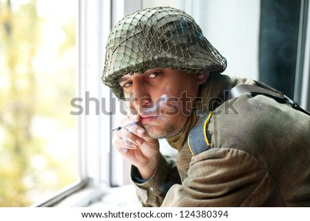 Soldier smoking near a window - stock photo