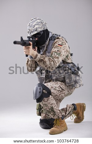 Soldier special forces with machine gun in a white studio - stock photo