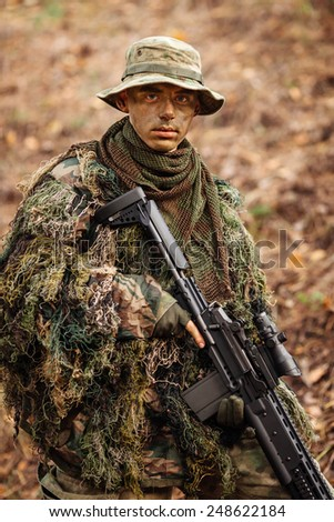 soldier stands with arms and looks forward - stock photo